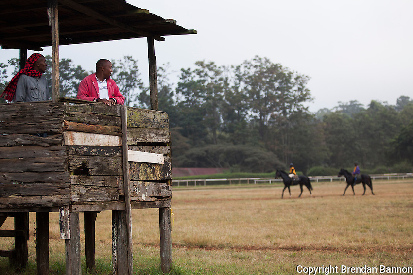 "Trainers Joe karari and Omesmus Mutua watched horses train in the early morning at Ngong Racecourse. "" we don't use binoclulars, our eyes are very sharp"" said Mutua. The trainers watch the horses and jockeys  for signs of how they are developing and working  as well as listening to the horses breathing. Nairobi, Kenya. March 13, 2013. Photo: Brendan Bannon"