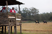 """Trainers Joe karari and Omesmus Mutua watched horses train in the early morning at Ngong Racecourse. """" we don't use binoclulars, our eyes are very sharp"""" said Mutua. The trainers watch the horses and jockeys  for signs of how they are developing and working  as well as listening to the horses breathing. Nairobi, Kenya. March 13, 2013. Photo: Brendan Bannon"""