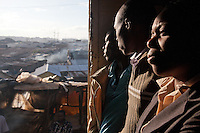 Passengers watch the city through the open doors of the 6:40 train from Athi River to Naiorbi.