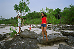 Three village girls standing on rocks on the beach near their home by the Tapajos river. The Floresta Nacional do Tapajos (FLONA), a 6500 km2 protected reserve, was home to several small communities which lived on the banks of the Rio Tapajos river. Most communities did not have electricity or running water and access to the villages was by unpaved dirt roads from Santarem and Highway BR163.