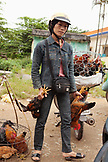 VIETNAM, Hue, portrait of a woman selling chickens on the side of the road in rural Hue