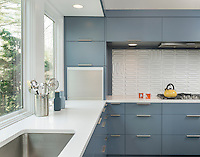 A contemporary kitchen with grey blue cabinets. A textured splashback is set behind a gas hob.