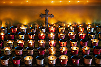 Votive candles in a Catholic devotional chapel.