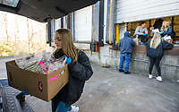 Lily Grace Hassebrock, 13, of Springdale volunteers to take orders to cars Saturday, March 21, 2020, at Kimball and Thompson Produce in Lowell. The business supplies fresh produce to the food service industry, including public schools, restaurants and hotels. With many of their usual clients closed due to the covid-19 pandemic, owner Chris Thompson says they are adapting to get their inventory directly to consumers who need it at wholesale prices. Thompson says he is also reaching out to the Northwest Arkansas Food Bank to make sure nothing goes to waste. <br /> <br /> The business began selling to the public Friday morning, and many shelves were already bare Saturday. Thompson says they will be working to keep their inventory updated as they navigate the temporary change to their business model. <br /> <br /> Staff and family members are pitching in to help fill orders curbside while minimizing personal contact and practicing strict sanitizing measures. Customers are asked to place orders ahead of time by calling 479-872-0200 or emailing orders@ktproduce.com. Pickup times are Monday through Saturday from 9 a.m. to 4 p.m., and Sunday from 11 a.m. to 2 p.m. at 305 S. Lincoln St. in Lowell. <br /> <br /> Check out nwaonline.com/200322Daily/ for today's photo gallery.<br /> (NWA Democrat-Gazette/Ben Goff)