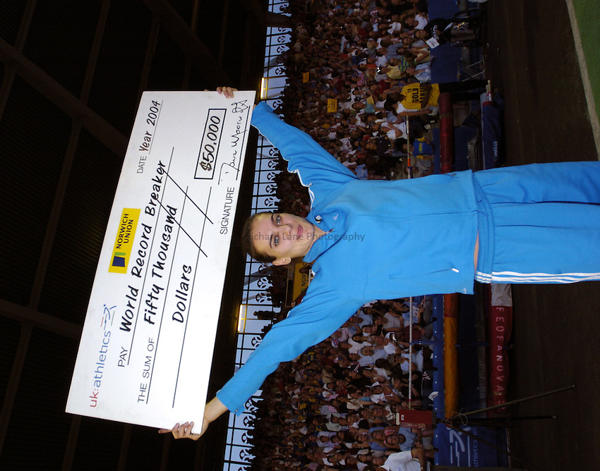 Photo: Richard Lane..Norwich Union London Grand Prix Athletics at Crystal Palace. 30/07/2004..Yelena Isinbayeva with a cheque  for $50,000 after achieving a new world record height of 4.90m in the womens pole vault.