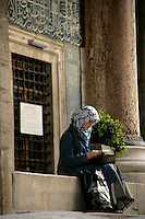 Muslim girl reading in the courtyard of the New Mosque, Istanbul, Turkey
