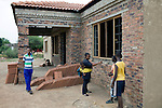 GA-MASEHLONG, SOUTH AFRICA - MARCH 28: Unidentified relatives stand outside the newly constructed house for Caster Semenya on March 28, 2010, in Ga-Masehlong, South Africa. Caster Semenya, age 19, a runner who won the 800 meters world cup title in Berlin, Germany in 2009. She was later gender tested as she blew away the competition. She has not competed in any race since then but she is still a role model for relatives and children in this rural poor village. She was raised in the traditional hut on the right and the newly constructed house is a gift from the local government. (Photo by Per-Anders Pettersson/Getty Images)