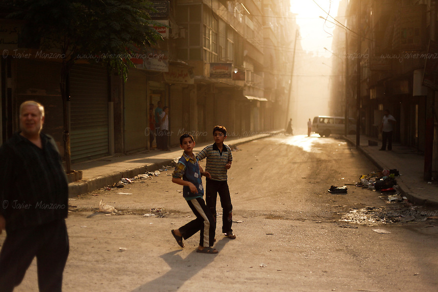 Civilians come out to the streets to survey the damage of the last mortar shell that hit the battered neighborhood of Sha'ar in the heart of Aleppo city on Tuesday, October 9, 2012. ..© Javier Manzano..