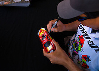 Jul. 26, 2014; Sonoma, CA, USA; NHRA funny car driver Cruz Pedregon signs a diecast model during qualifying for the Sonoma Nationals at Sonoma Raceway. Mandatory Credit: Mark J. Rebilas-