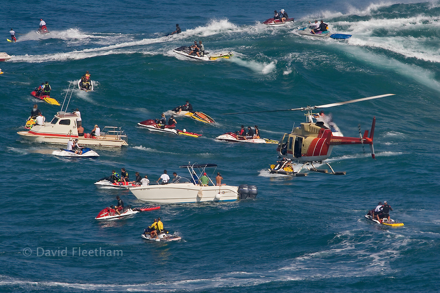 A helicopter filming tow-in surfing at Peahi (Jaws) off Maui. Hawaii.