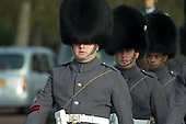 Guards wearing grey winter uniform march down the Mall towards Buckingham Palace