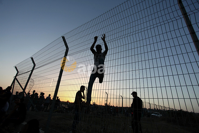 Palestinian protesters climb the border fence during clashes with Israeli troops between Israel and the Gaza Strip on October 14, 2015 east of Bureij in central Gaza. The outbreak of violence between Palestinians and Israeli forces in recent weeks has worsened in October, raising fears of a third intifada, or uprising. Photo by Ashraf Amra