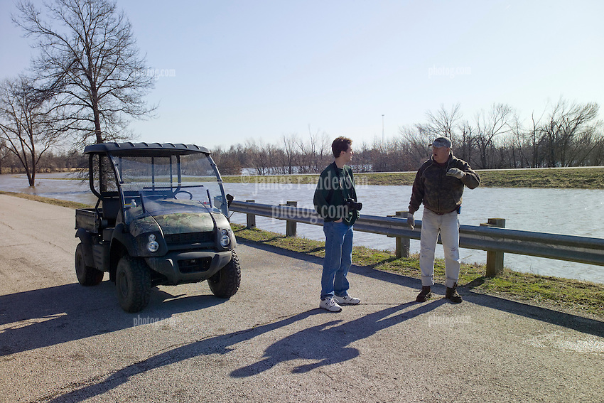 Pete Greeley, traveler, and John North, local resident, discussing the Bush Creek Marsh Arch Rainbow Bridge on Old Route 66 Riverton, KS as the area is experiencing the results of a 100 year flood.