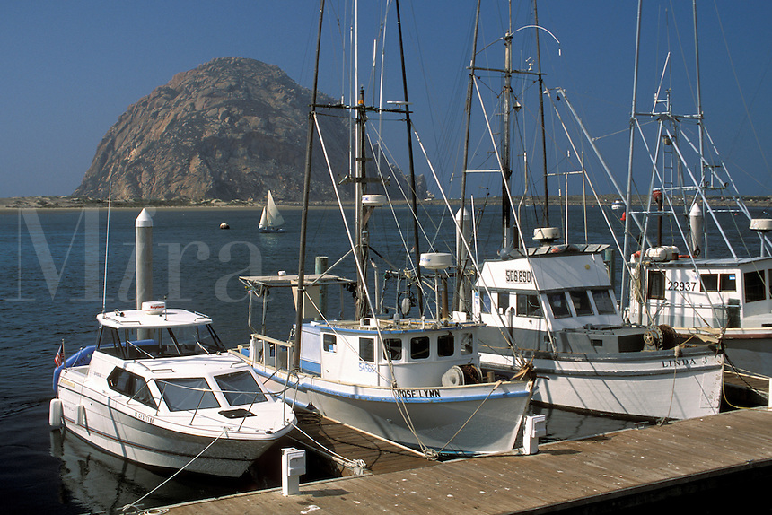 Commercial fishing boats docked at wharf marina in and Morro Rock, Morro Bay, San Luis Obispo county coast, California.