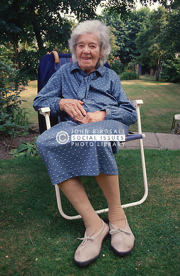 Portrait of elderly woman sitting outside in garden smiling,