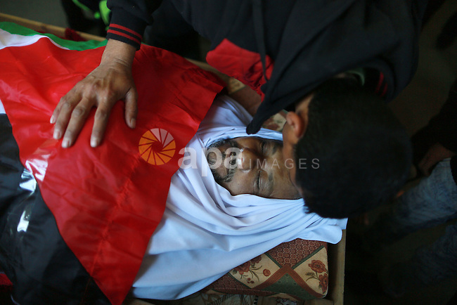 A Palestinian man kisses the face of 48-year-old Yussef al-Buhairi draped in the Palestinian flag during his funeral in the al-Maghazi refugee camp, located in in the centre of the Gaza Strip, on December 28, 2015. Buhairi who was wounded at the Gaza border during clashes with the Israeli army the previous week died early on December 27 from his injuries, the Gaza health ministry said. Photo by Yasser Qudih