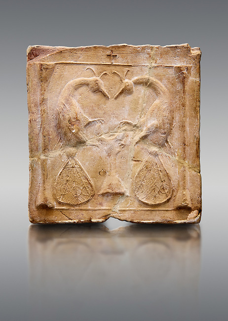 6th-7th Century Eastern Roman Byzantine  Christian Terracotta tiles depicting two Peacocks - Produced in Byzacena -  present day Tunisia. <br /> <br /> <br /> The patterns of peacock tails contain round decorations. These were seen to be the symbolic eyes of omnipotence and often ascribed to the Archangel Michael. The peacock's feather is sometimes associated with St. Barbara Also, The peacock, (due to an ancient myth that Peacock flesh did not decay), is seen as a symbol of immortality.<br /> <br /> These early Christian terracotta tiles were mass produced thanks to moulds. Their quadrangular, square or rectangular shape as well as the standardised sizes in use in the different regions were determined by their architectonic function and were designed to facilitate their assembly according to various combinations to decorate large flat surfaces of walls or ceilings. <br /> <br /> Byzacena stood out for its use of biblical and hagiographic themes and a richer variety of animals, birds and roses. Some deer and lions were obviously inspired from Zeugitana prototypes attesting to the pre-existence of this province's production with respect to that of Byzacena. The rules governing this art are similar to those that applied to late Roman and Christian art with, in the case of Byzacena, an obvious popular connotation. Its distinguishing features are flatness, a predilection for symmetrical compositions, frontal and lateral representations, the absence of tridimensional attitudes and the naivety of some details (large eyes, pointed chins). Mass production enabled this type of decoration to be widely used at little cost and it played a role as ideograms and for teaching catechism through pictures. Painting, now often faded, enhanced motifs in relief or enriched them with additional details to break their repetitive monotony.<br /> <br /> The Bardo National Museum Tunis, Tunisia.   Against a grey background.
