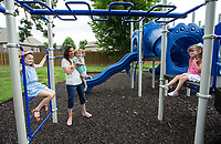 Whitney Killebrew plays Friday, June 26, 2020, with her daughters Audrey Killebrew (from left), 7, Joelle Killebrew, 1, and Sloane Killebrew, 4, and at the park in their Bentonville neighborhood. Go to nwaonline.com/200627Daily/ to see more photos.<br /> (NWA Democrat-Gazette/Ben Goff)