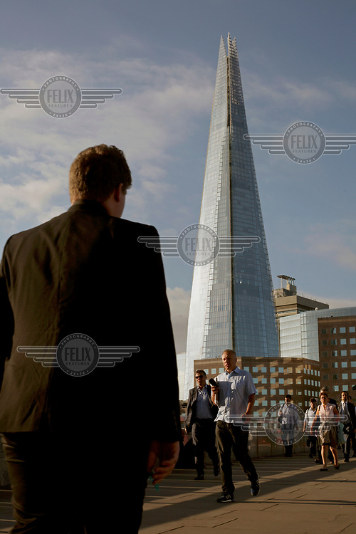 People walking across London Bridge on their way to work. Rising behind them is the Shard building.