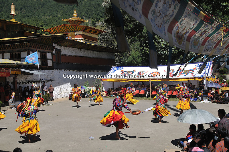 """Monks performing at Bumthang Tsechu at Tamshing Monastry. The Tshechu is a festival honouring Guru Padmasambhava, """"one who was born from a lotus flower."""" This Indian saint contributed enormously to the diffusion of Tantric Buddhism in the Himalayan regions of Tibet, Nepal, Bhutan etc. around 800 AD. He is the founder of the Nyingmapa, the """"old school"""" of Lamaism which still has numerous followers. The biography of Guru is highlighted by 12 episodes of the model of the Buddha Shakyamuni's life. Each episode is commemorated around the year on the 10th day of the month by """"the Tschechu"""". The dates and the duration of the festivals vary from one district to another but they always take place on or around the 10th day of the month according to the Bhutanese calendar. During Tshechus, the dances are performed by monks as well as by laymen. The Tshechu is a religious festival and by attending it, it is believed one gains merits. It is also a yearly social gathering where the people, dressed in all their finery, come together to rejoice. Arindam Mukherjee."""