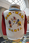 Garden City, New York, USA. December 12, 2015. A vintage Pac-Man Mania colorful baseball shirt and cap from 1980's are on display with other arcade memorabilia during Opening Day of Arcade Age exhibit, where visitors experience playing authentic classic games in arcade set up at Cradle of Aviation Museum in Long Island. On shirt, Pac-Man characters play musical instruments. Exhibit runs from Dec. 12, 2015 through April 3, 2016.