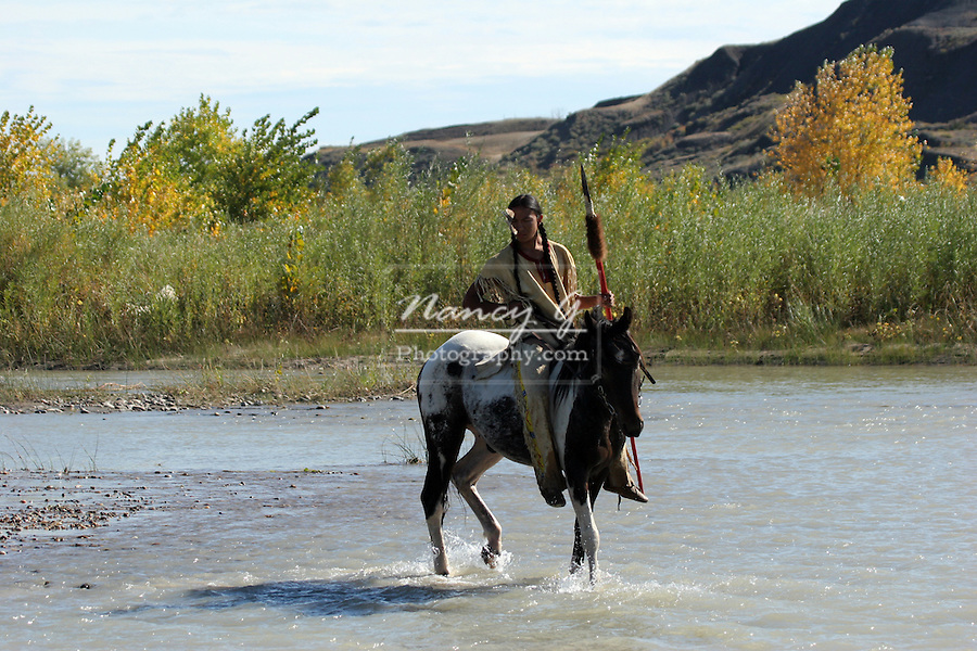 A Native American Sioux Indian on horseback riding across a stream in South Dakota