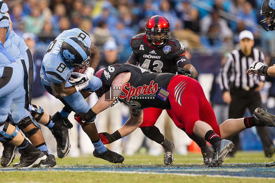 T.J. Logan (8) of the North Carolina Tar Heels is tackled by Mitch Meador (46) of the Cincinnati Bearcats during the Belk Bowl at Bank of America Stadium on December 28, 2013 in Charlotte, North Carolina.  The Tar Heels defeated the Bearcats 39-17.   (Brian Westerholt/Sports On Film)