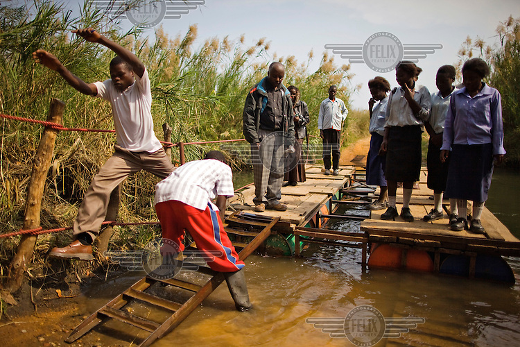 Children from grades 4 and 5 at Chalilo school in Sereje district, take a pontoon across a river in search of hippos on their first safari in Kasanka National Park. Local schools and women's groups are regularly brought into Kasanka, which is unique in the country and unusual in Africa as it is privately managed and owned by a trust. People are able to see animals flourishing in land which was once free reign for poachers. Combined with anti-poaching scouts, the education programme is on the frontline of conservation methods in the park, showing local people wild animals in their natural habitat.