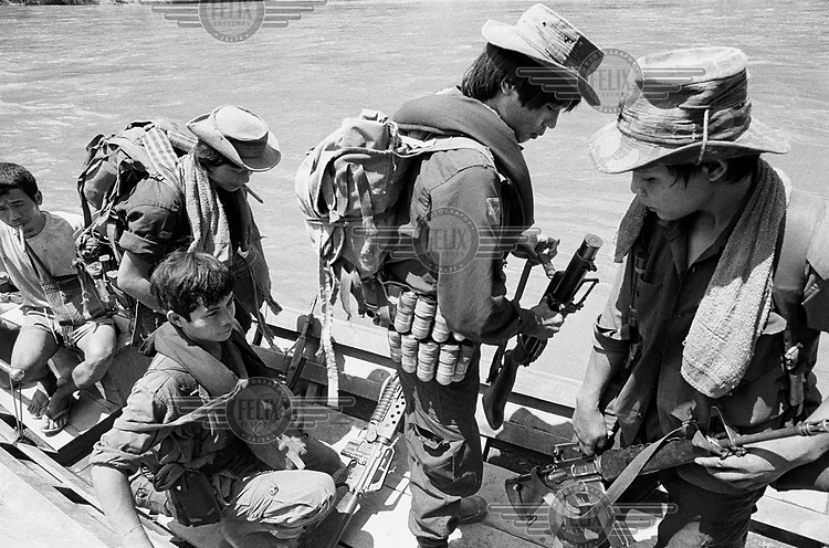 Karenni Army soldiers leaving for the frontline in a long-tail boat along the Pai River. Fighting rages close by as Burma Army forces try to recapture an outpost recently overrun by Karenni forces.