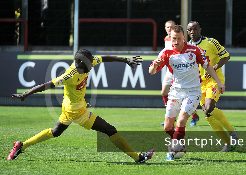 Moeskroen Peruwelz - SK Sint-Niklaas  : Jeremy Huyghebaert aan de bal voor de tacklende Ameth Gaye (links).foto VDB / BART VANDENBROUCKE