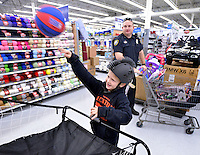 STAFF PHOTO BEN GOFF  @NWABenGoff -- 12/09/14 Keagon (CQ) Bailey, 7, tries out a basketball shooting game and a bicycle helmet while shopping with Bentonville Police Cpl. Ryan Simmons during the Bentonville Fraternal Order of Police's annual Shop With a Cop event at the Walmart Supercenter in Bentonville on Tuesday Dec. 9, 2014. Fifty elementary school children from Bentonville schools went shopping with a police officer to find gifts for themselves and their family.
