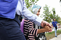 Pictured: A young migrant girl is escorted by hand on her first day at the Tavros 2nd Primary school in Athens Greece. Monday 10 October 2016<br /> Re: Children of refugees have started school in various parts of Greece.
