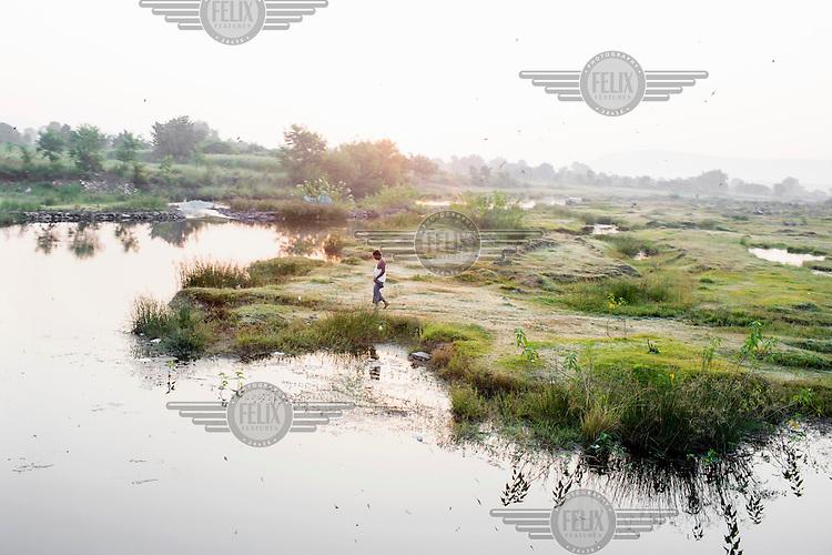 A man walks near a pond in the Panna Tiger Reserve in Madhya Pradesh.