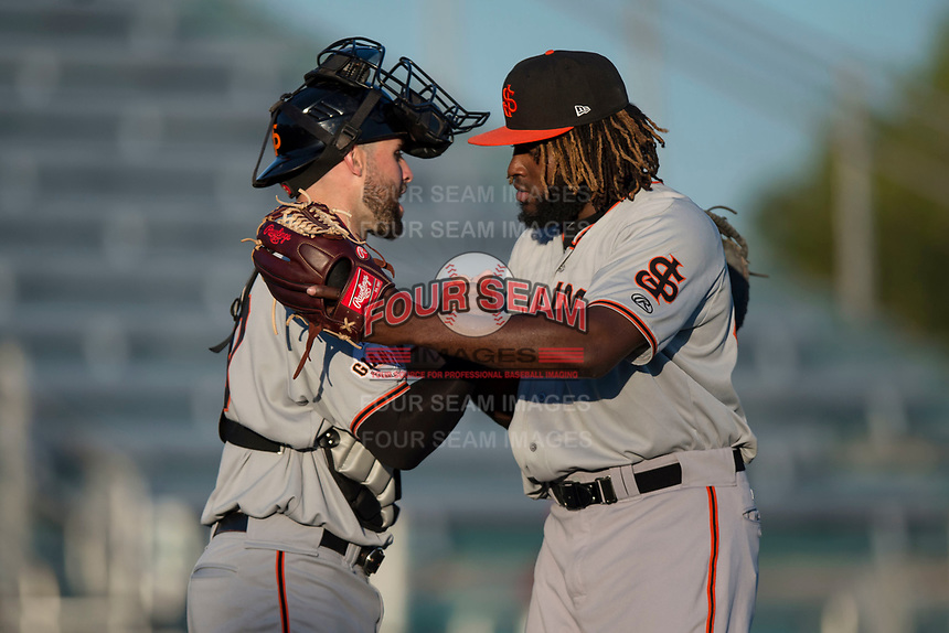 San Jose Giants relief pitcher Rodolfo Martinez (40) and catcher Matt Winn (10) celebrate after a California League game against the Modesto Nuts at John Thurman Field on May 9, 2018 in Modesto, California. San Jose defeated Modesto 9-5. (Zachary Lucy/Four Seam Images)
