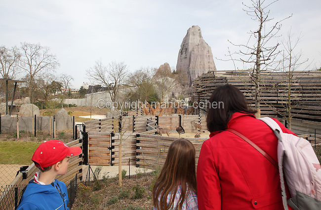 A family viewing the West African giraffes (Giraffa camelopardalis), ostriches (Struthio camelus) and Greater kudus (Tragelaphus strepsiceros) in their enclosures, with the Grand Rocher or Great Rock in the background and the giraffe indoor enclosure building on the right, in the Zone Sahel-Soudan at the new Parc Zoologique de Paris or Zoo de Vincennes, (Zoological Gardens of Paris or Vincennes Zoo), which reopened April 2014, part of the Musee National d'Histoire Naturelle (National Museum of Natural History), 12th arrondissement, Paris, France. Picture by Manuel Cohen
