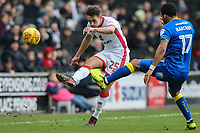 Callum Brittain of MK Dons passes the ball under pressure from Andy Barcham of AFC Wimbledon during the Sky Bet League 1 match between MK Dons and AFC Wimbledon at stadium:mk, Milton Keynes, England on 13 January 2018. Photo by David Horn.
