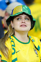 A Dejected Brazil fan cries after the final whistle