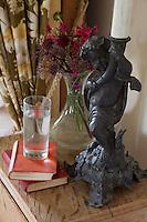 A jaunty cherubic figure holds a bedside lamp aloft