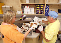 NWA Democrat-Gazette/DAVID GOTTSCHALK   Sonia Cross (left), kitchen manager, and Steve Guthrie, food transport, box hot meals for delivery Monday, August 10, 2015 for Meals on Wheels for Farmington, Greenland and West Fork in the kitchen of the Farmington Senior Center. The program has expanded from 43 to 70 clients over the past 18 months that receive the hot meals five days a week with additional frozen dinners for weekend and holiday meals.