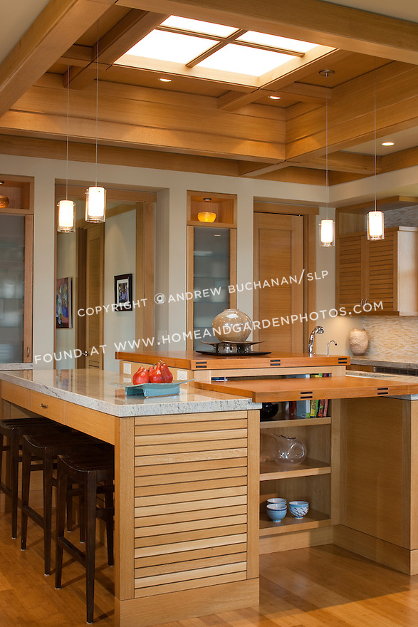 A unique three-part kitchen island is the heart of this open, airy kitchen. this image is available through an alternate architectural stock image agency, Collinstock located here: http://www.collinstock.com