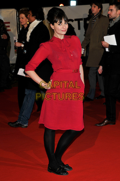 "GIZZI ERSKINE .Attending the ""Invictus'"" UK Film Premiere at the Odeon West End cinema, Leicester Square, London, England, January 31st, 2010..arrivals full length dress sleeves hands in black tights shoes red moccasins flats loafers in pockets pussybow pussy  bow .CAP/PL.©Phil Loftus/Capital Pictures"