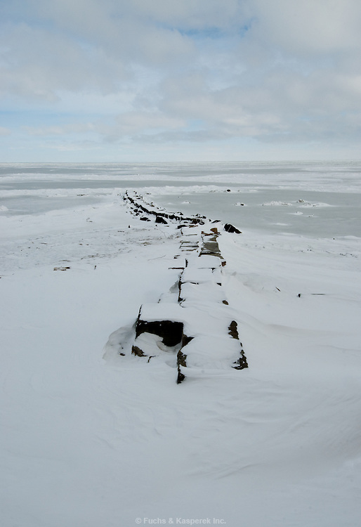A breakwall leads into a frozen Lake Erie on an icy mid-winter day.