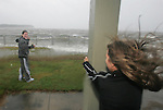 A girl and her mother play in the winds of the approaching Hurricane Ivan while her mother Denise Hickman (R) hangs onto a concrete pole as the winds approach 50 miles per hour at Wayside Park in Pensacola September 15, 2004.