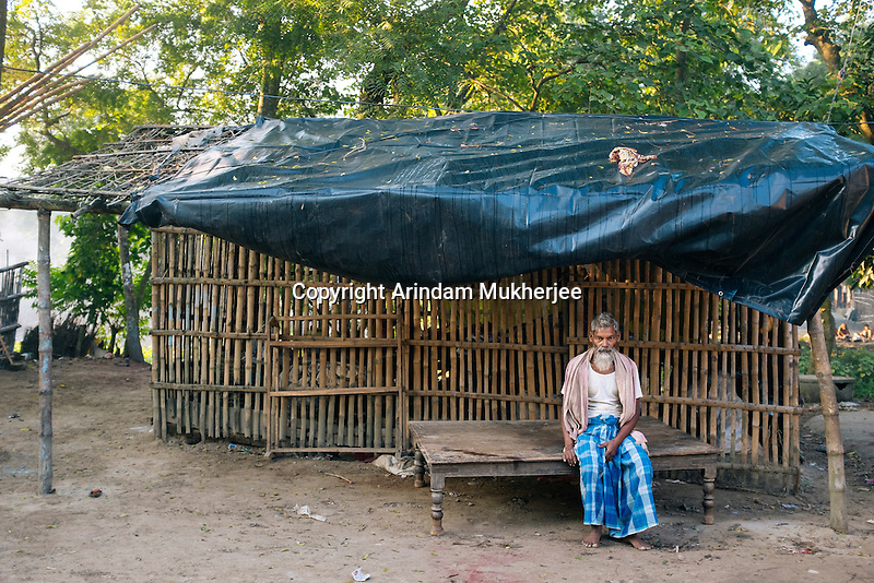 Seikh Iliyaas (51) sits in front of his make shift house. Iliyaas had his house next to the Ganga and in the September 2014 erosion lost it to the river.A daily wage labour, he now lives in a neighbour's poultry room  with his wife. Kholsi village, Murshidabad District, West Bengal, India.