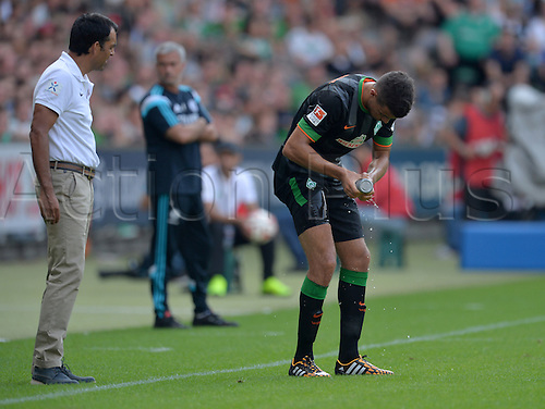 03.08.2014. Bremen, Germany.  Werder's Franco di Santo cools his leg watched by Werder's coach Robin Dutt (L) during the soccer friendly match between Werder Bremen and FC Chelsea at Weserstadion in Bremen, Germany.