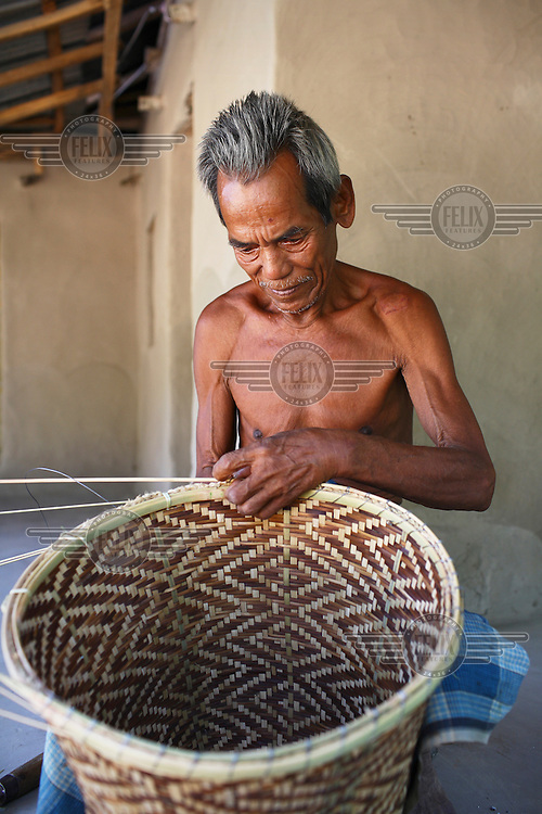 A Garo man weaving a basket. The Garo (or Mandi, as they refer to themselves) are an ethnic minority thought to be of Tibeto-Burmese origin. Prior to British rule they were mostly anamists but missionary work led the majority to convert to Christianity. The Garo of the Madhupur forest have long been under the threat of eviction by the government and the forest that they gain much of their livelihood from is being rapidly destroyed by unregulated logging.