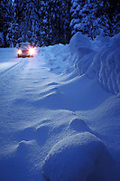 mini van with headlights on driving on snow covered road at dusk. California.