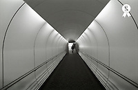 England, London, Gatwick airport, Passenger at end of airport walkway, rear view (Licence this image exclusively with Getty: http://www.gettyimages.com/detail/sb10068805r-001 )