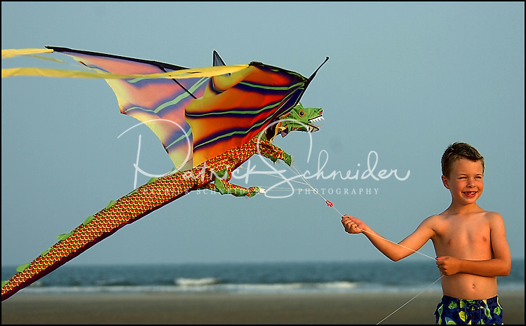 A young boy (model released) flies a kite along an ocean beach on a windy evening. Photo taken along a South Carolina beach on the Atlantic Ocean, but could represent a beach scene anywhere.