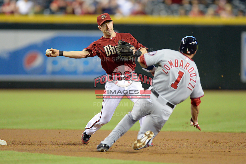 Arizona Diamondbacks shortstop Willie Bloomquist (18) attempts to turn a double play as Steve Lombardozzi (1) slides in during a game against the Washington Nationals at Chase Field on September 29, 2013 in Phoenix, Arizona.  Arizona defeated Washington 3-2.  (Mike Janes/Four Seam Images)